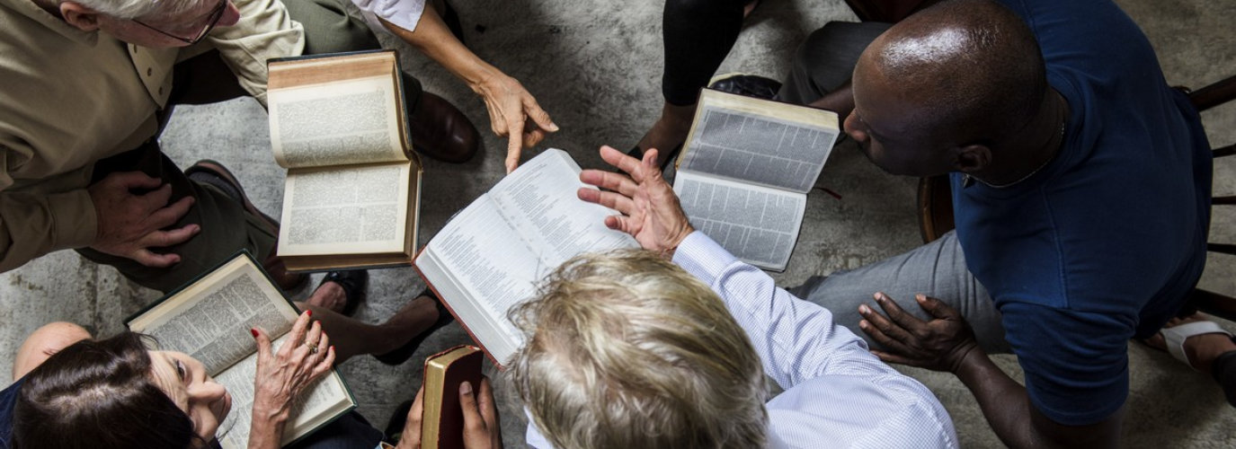 people reading a bible indoor