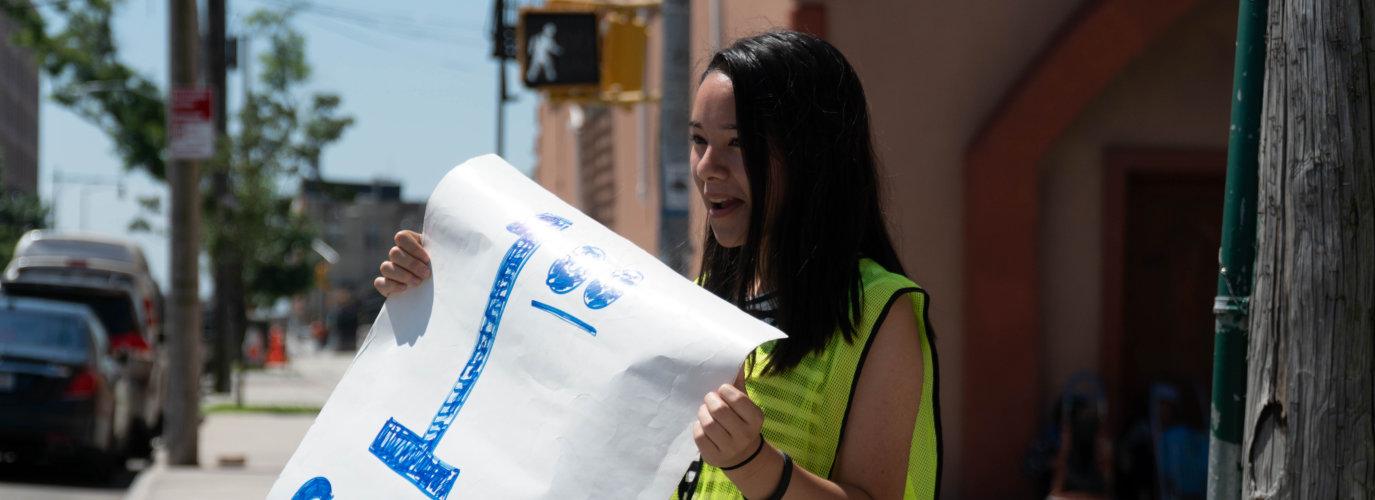 girl holding a banner on street